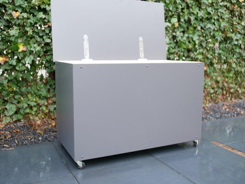 Kissenbox im Garten mit offener Klappe